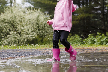 USA, Hide Park, Vermont. Little two year old blonde girl wearing a pink hooded sweater and pink rubber boots walks through puddles on a gravel road after heavy rain fall.