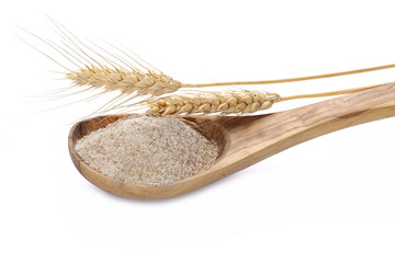 Integral flour in wooden spoon and wheat ears, with grain isolated on white background
