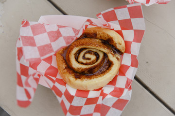 USA, New Hampshire. A cinnamon roll in red and white checkered paper.