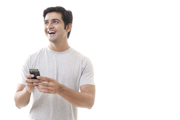 Cheerful young man holding cell phone on white background