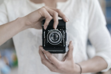 Woman's hands holding vintage camera