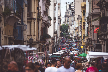The narrow street of Buenos Aires is crowded with people. Shevelev.