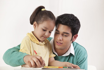 Young father helping her daughter in drawing