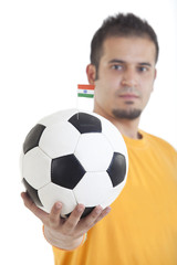 Portrait of young man holding soccer ball with small Indian flag on it over isolated on white background
