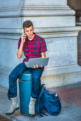 Young American Man working on laptop computer, talking on cell phone on street in New York.
