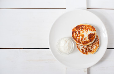 Fried cottage cheese fritters with sour cream on a white plate