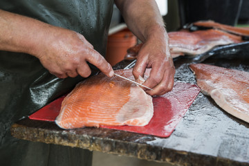 Fishmonger preparing fillets from whole salmon