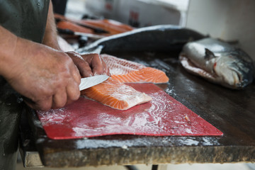 Fishmonger preparing small fillets from whole salmon