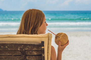 Young woman drinking coconut milk on Chaise-longue on beach.