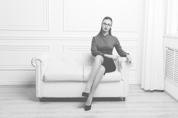 Beautiful woman in red shirt and eyeglasses sitting on a sofa, Monochrome image