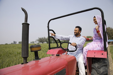 Indian couple on tractor with man pointing at something