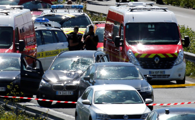 Police and rescue forces are seen at the scene where the man suspected of ramming a car into a group of soldiers on Wednesday in a Paris suburb has been shot and arrested on the A16 motorway