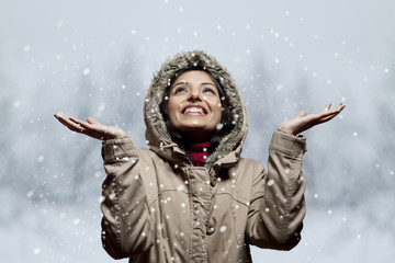 Young woman enjoying snow fall