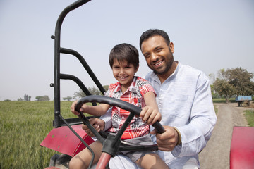 Portrait of a happy father and son driving tractor