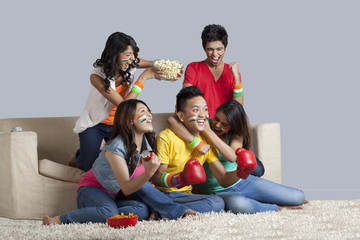 Friends enjoying together while watching a boxing match at home