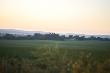 Morning landscape. Sunrise behind the village on the field.