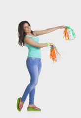 Full length portrait of young woman in casual wear holding tricolor pom poms over white background
