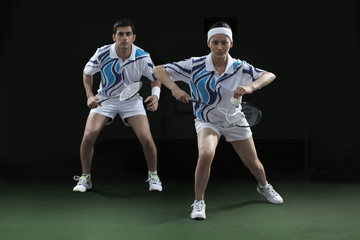 Portrait of man and woman playing badminton doubles at court