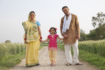 Full length portrait of a young girl with her family walking on rural road