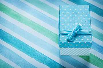 Packed gift box on blue striped table cloth holidays concept