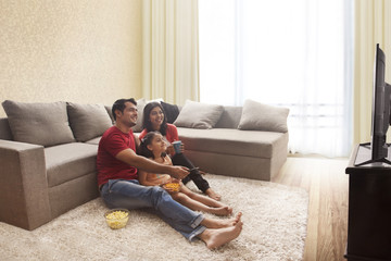 Family sitting on floor watching television