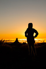 Silhouette girl in backlight on mountain summit at sunset