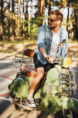 Concentrated young bearded man sitting on scooter outdoors