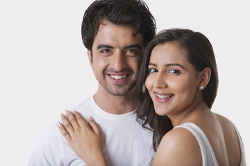 Portrait of young couple smiling against white background