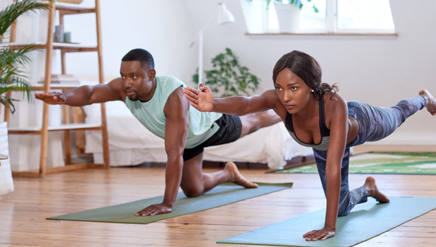 African couple exercising doing yoga together at home