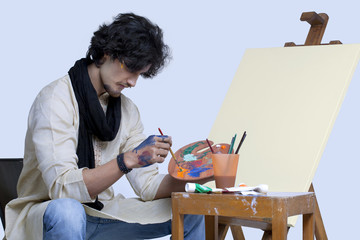 Young artist mixing colors against colored background