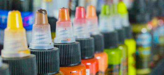 Multiple bottles with colorful inks for tattoo. Side view. Close-up