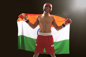 Happy Indian male boxer with national flag standing against black background