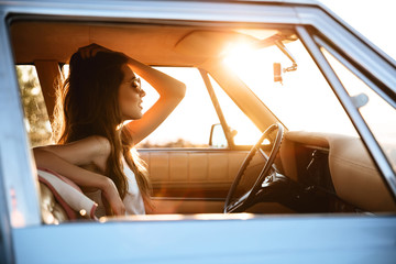 Side view of a woman sitting inside a retro car
