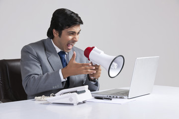 Furious businessman shouting through megaphone over laptop at desk against gray background