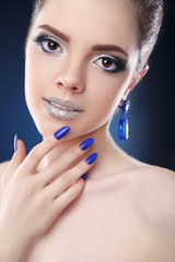 Glitter lips Makeup. Manicure nails. Fashion glamour girl model studio close up portrait. earrings jewelry background