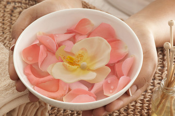 Rose petals and orchid in a bowl with reed diffuser