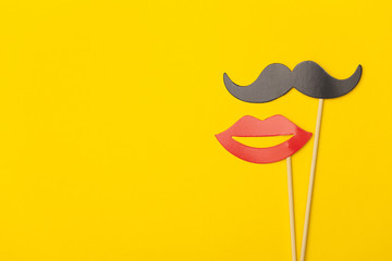 Moustache and lips on a stick on a bright yellow background