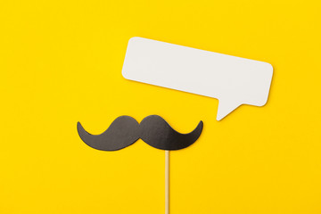 Moustache on a stick with a speech bubble on a bright yellow background