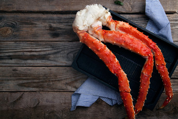 Fresh crab claws on black tray on vintage wooden background. Composition with copy space