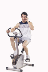 Portrait of a young man talking on mobile phone while exercising over white background