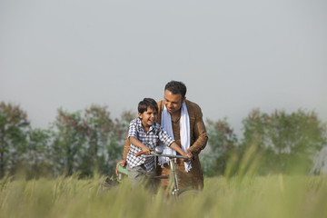 Father teaching son to ride cycle in the field