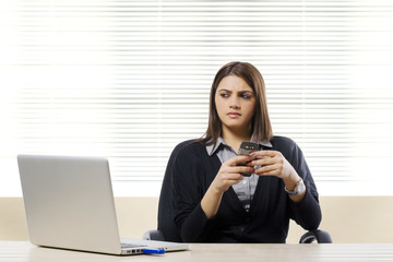 Businesswoman thinking while holding a mobile phone
