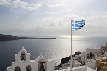 Church with bells in Santorini Greece and greek flag