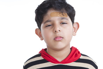 Portrait of little boy with band-aid on forehead