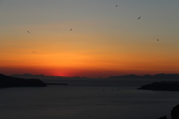 Golden Orange Sunset Views in the Greek Island of Santornini with Birds Flying in the Dark Skies