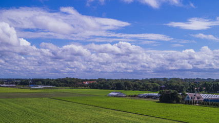 flat dutch farmland with a clear blue sky and white puffy clouds, farms and buildings in de distance like farms and sheds. The Netherlands