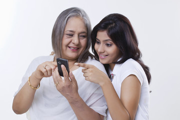 Close-up of a girl with her grandmother holding a mobile phone