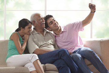 Grandfather and grandchildren taking a photograph of themselves