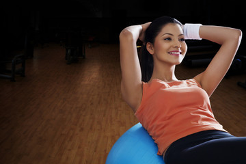 Happy young woman balancing on exercise ball with hands behind head