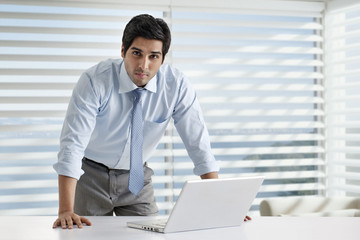 Portrait of young businessman standing by desk with laptop